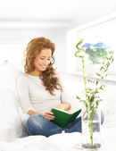 Young and beautiful girl reading book on the modern sofa — Stock Photo