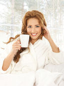 Young attractive woman in towel drinks coffee — Stock Photo