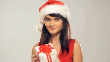 A happy woman in a Christmas hat holding a present — Stock Video