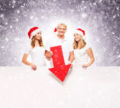 Three happy teenagers in red Christmas hats posing next to a white banner — ストック写真