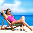 A young brunette woman in a white swimsuit relaxing on the beach — Stock Photo #36881451