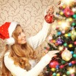 Stock Photo: Beautiful teenager girl decorating the Christmas tree