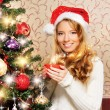 Beautiful teenager girl decorating the Christmas tree — Stock Photo #36881599