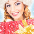 Portrait of a young woman in winter clothes holding a present — Stock Photo
