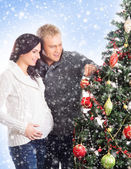 A pregnant mother and a happy father posing near the Christmas tree — Stock Photo
