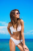 A young brunette woman in a white swimsuit relaxing on the beach — Stock Photo