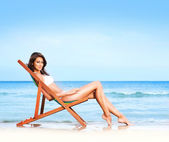 Young, beautiful, sporty and sexy woman relaxing on the beach — Stok fotoğraf