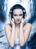 Fashion shoot of a young woman listening to the music in headphones — Stock Photo