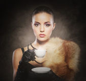 Portrait of a young woman in fur drinking coffee — ストック写真