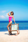 A woman in a swimsuit on a sea resort background — Stock Photo