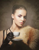 Portrait of a young woman in fur drinking coffee — Stock Photo