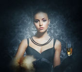 A young woman in a dress drinking champagne on a retro background — Stock Photo