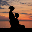 A woman getting traditional Thai stretching massage by a therapist on the sunset — Stock Photo #39824909