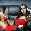 Woman in red dress on the leather sofa — Stock Photo