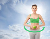 Young attractive sporty woman with a green apple over the heaven — Stok fotoğraf