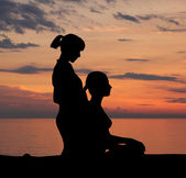 A woman getting traditional Thai stretching massage by a therapist on the sunset — Stock Photo