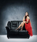Woman in red dress sitting on the black leather sofa — Stock Photo