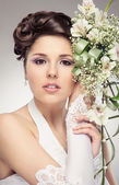 Young and beautiful bride standing with the flower bouquet over — Stock Photo