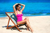 A young woman in a swimsuit relaxing on the beach — Stock Photo