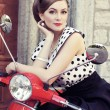 Young and sexy woman with her motor scooter — Stock Photo #42520517