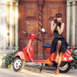 Young and sexy woman with her motor scooter — Stock Photo #42520523