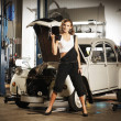 Young and sexy woman repairing a retro car in a garage — Stock Photo