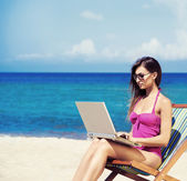 A young woman relaxing with a laptop on a beautiful beach — Stock Photo