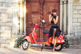 Young and sexy woman with her motor scooter — Stock Photo