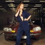 Woman repairing a retro car in a garage — Stock Photo