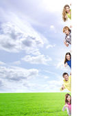 Kids with the blank banner. Perfect space to put any text. — Stock Photo