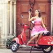 Young and sexy woman with her motor scooter - retro style image. — Stock Photo