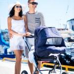 Couple walking with baby pram — Stock Photo