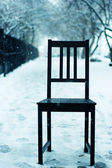 Black chair outdoors snowed up — Stock Photo