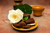 Chocolate with white rose — Stock Photo