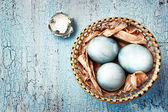 Blue easter eggs in a wattled plate on a textured background. Ru — Stock Photo