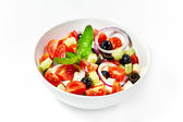 Light greek salad with fresh vegetables, garnished with basil. W — 图库照片