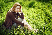Beautiful young woman is sitting in the grass. Thinking and rela — Stock Photo