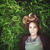 Beautiful young meditative woman in the grass. Instagram retro e — Stock Photo