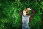 Beautiful meditative young woman lying in the grass. Summer, fre — Stock Photo