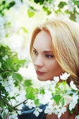 Portrait of beautiful young woman in flowers — Stock fotografie