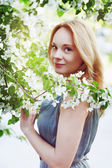 Fashion portrait of a young beautiful woman in flowers — Stock Photo