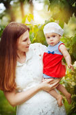 Beautiful young mother and daughter in summer park — Stock Photo
