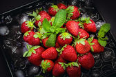 Ripe strawberry on ice with mint leaf — Zdjęcie stockowe