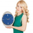 Foto Stock: Unhappy young womwith horror looks at clock on white background.