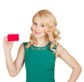 The beautiful blonde in a green dress holds a card — Stock Photo