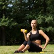 The beautiful blonde in park with dumbbells — Stock Photo