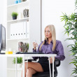 Businesswoman text messaging in bright office — Stock Photo
