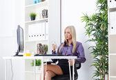 Affärskvinna textmeddelanden i ljusa kontor — Stockfoto