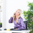 A beautiful young woman in an Office talking on the phone — Stockfoto