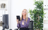 The beautiful girl at office at the computer with reader a thumb up — Stock Photo